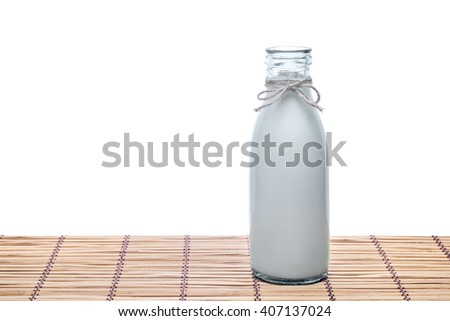 Old style bottle of milk on rustik wooden table Isolated on white background. - stock photo