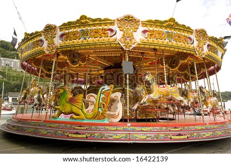 old style fairground carousel ride in holiday town - stock photo