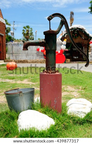 Old style hand water pump standing outdoor
