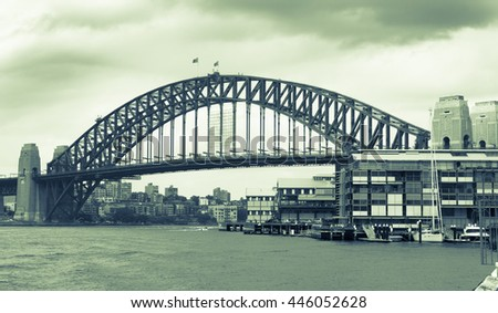 old style image gritty tones Sydney Harbor Bridge, Australia with darkening rain clouds gathering above split tone image green hue