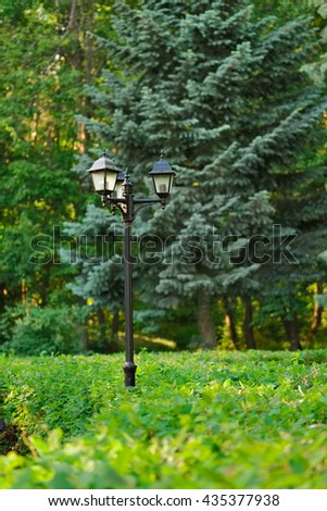 Old style lamp post in green summer park - stock photo