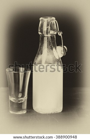 Old style monochrome image with pale vignette of limoncello bottle standing next to aperitif glass