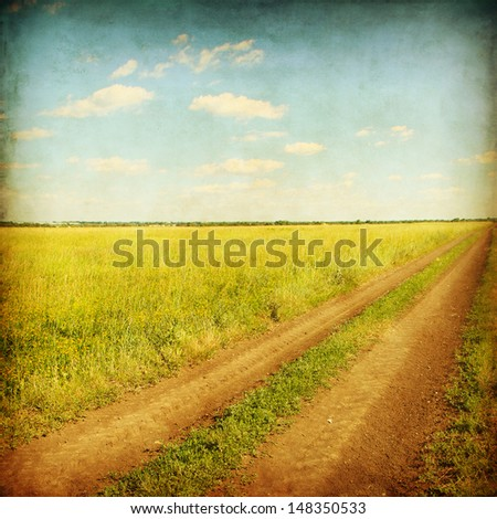Old style photo of rural road in the grass field.
