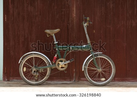 old style rusty green bicycle and wood doorSubjects