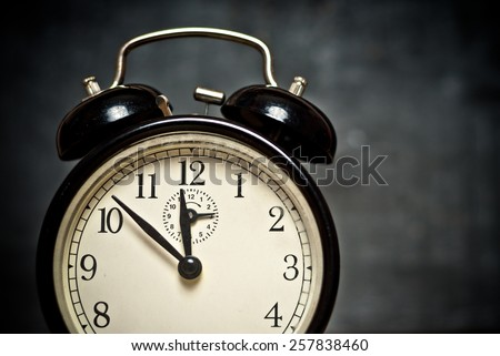 Old style vintage beige brown faced black metal alarm clock shows the time on dark gray background, close up image - stock photo