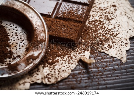 Old styled silver sieve with cocoa powder on chocolate bar, rustic style - stock photo