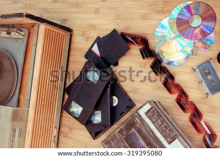 Old subjects of 80-90 years: a record player, video of the cartridge, disks, the cartridge and a film on a wooden background - stock photo