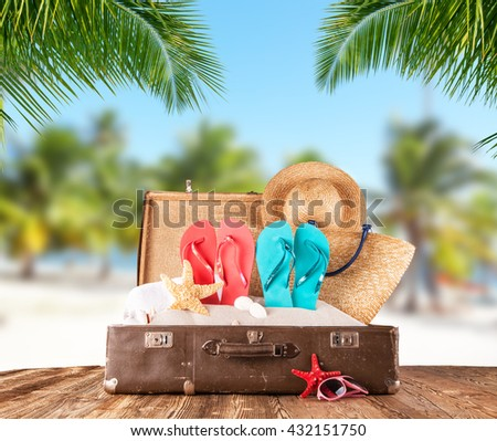 Old suitcase on tropical beach with palm leaves on background, travel concept - stock photo