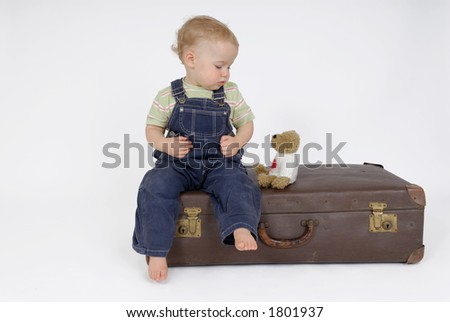 Old suitcase with little child - stock photo