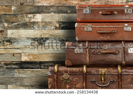 Old suitcases against wooden wall background or texture with copyspace - stock photo