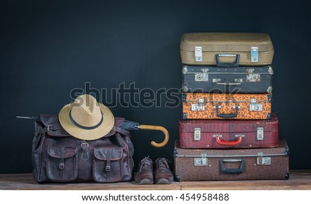 old suitcases and straw hat on a dark studio background