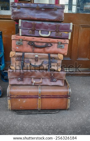 Old suitcases on trolleys in a station - stock photo