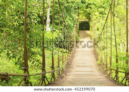 Old suspension bridge in forest,select focus with shallow depth of field:ideal use for background. - stock photo