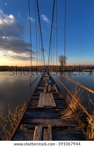 Old suspension bridge with broken wooden planks during sunset.