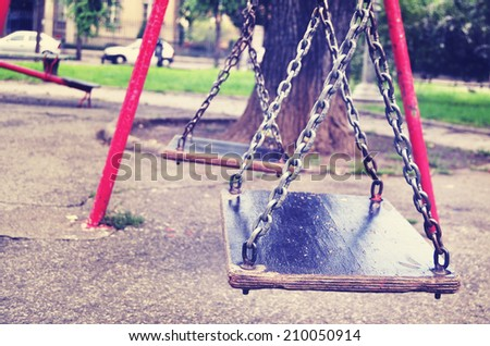 Old swings on a playground in retro style - stock photo