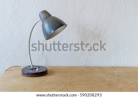 Old table lamp on wooden table stock photo edit now 590208293 old table lamp on a wooden table in front of a white wall table lamp aloadofball Image collections
