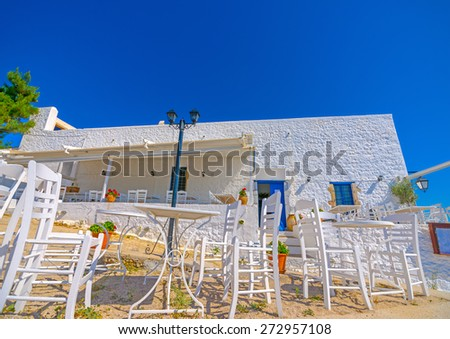 old tables and chairs by the sea in Spetses island in Greece - stock photo