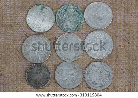 old taler silver coins on sacking background - stock photo