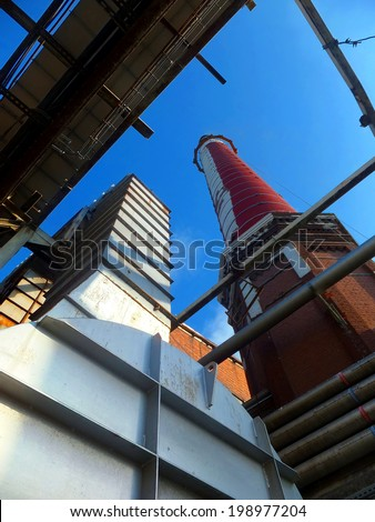old, tall industrial chimney of brick and exhaust ducts on the background of a cloudless afternoon sky - stock photo