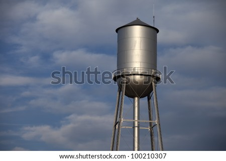 Old tall silver water tower with cloudy blue sky background