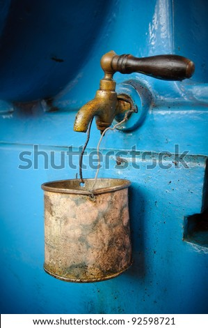 Old tap with rusty mug - water supply shortage - stock photo