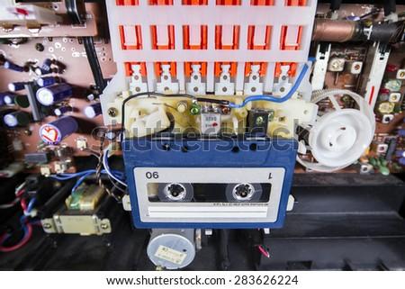 old tape cassette inside a broken hifi system - stock photo