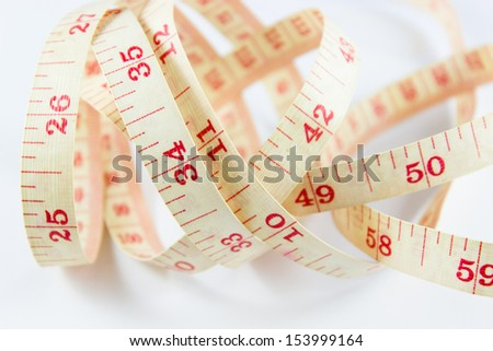 Old tape measure on rolled up on white background - stock photo