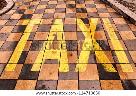 Old taxi sign on cobblestones - stock photo