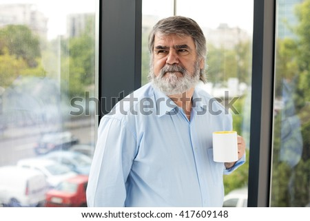 old teacher with gray beard and blue shirt drinking coffee next to a window - stock photo