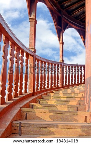 Old teak wood outdoor spiral staircase. - stock photo