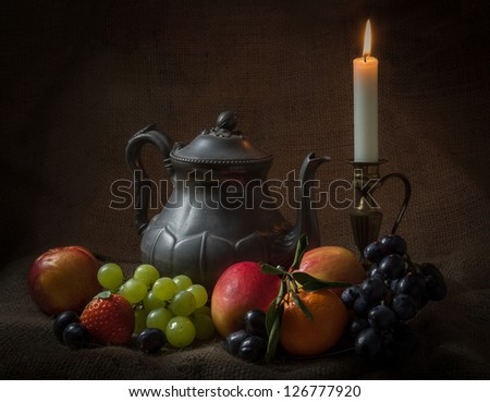 Old Teapot and lit candle with several fruit against a hessian background - stock photo