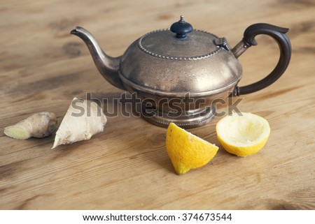 old teapot with lemon and ginger on wooden table - stock photo