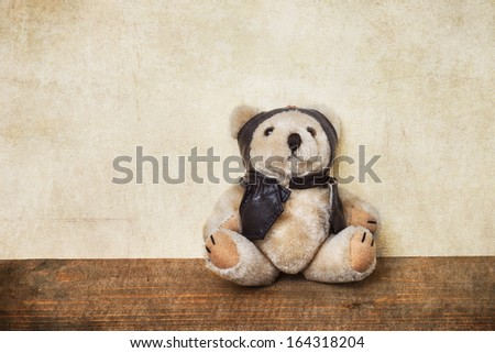 old teddy bear dressed as a pilot - stock photo