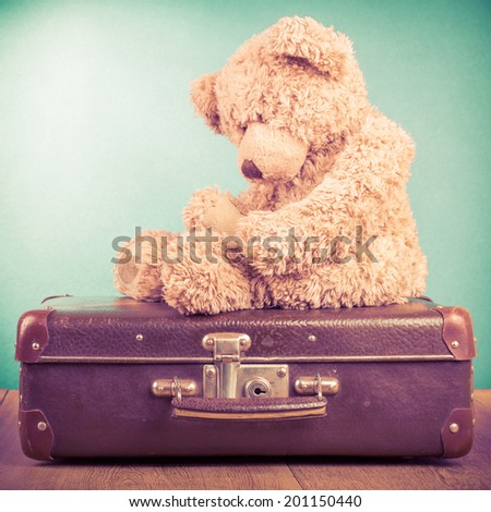 Old Teddy Bear toy sitting on retro suitcase - stock photo