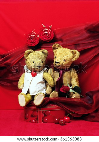 Old teddy bears couple sitting on red background