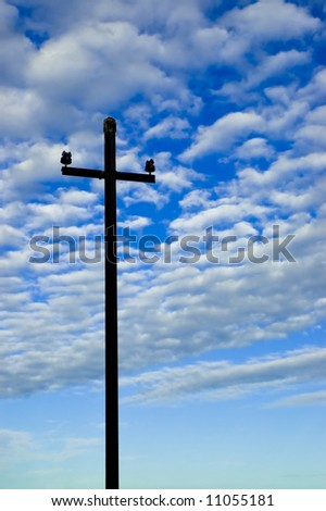 Old telegraph pole silhouetted against the sky.