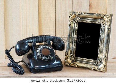 Old telephone and empty picture frame. - stock photo
