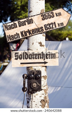 old telephone and signposts in the tree - stock photo