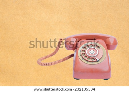 old telephone on paper background - stock photo