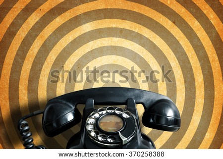 Old telephone on vintage paper background. - stock photo