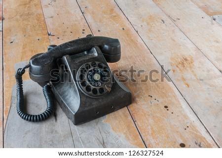Old telephone on wood background - stock photo