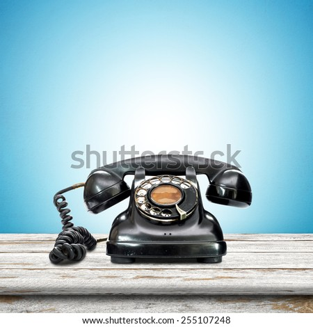 Old telephone put on the wooden in blue wallpaper room. - stock photo