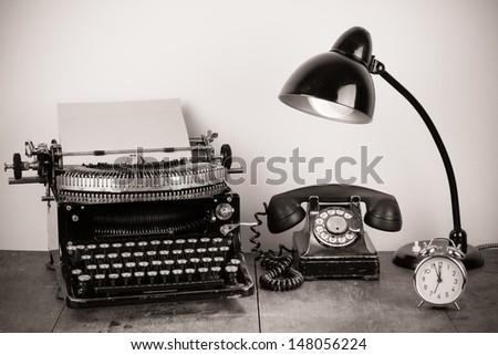 Old telephone, vintage typewrite, retro lamp, alarm clock on table - stock photo
