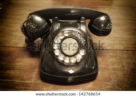old telephone with rotary dial on old wooden - stock photo