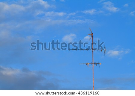 old television antenna with blue sky background.