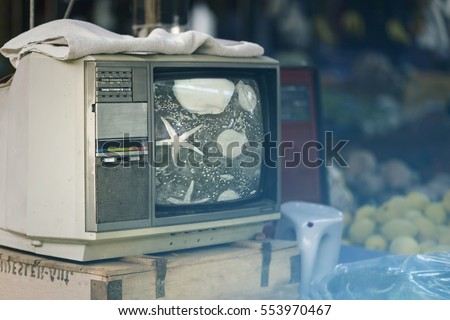 Old television on wooden cabinet. Toned