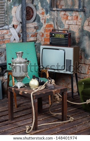 Old television, radio and wooden table with samovar in very old house. - stock photo