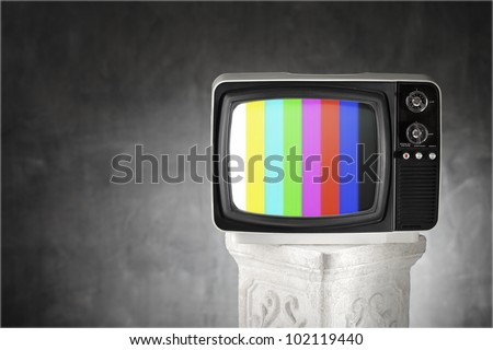 Old television with color bars on a plaster column.