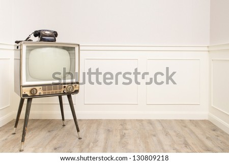 Old Television with 4 legs in the corner of vintage room and a black old telephone on it - stock photo