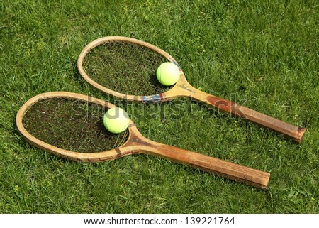 Old tennis rackets on grass court - stock photo